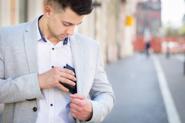 young businessman pull out his wallet - leder portemonnaie herren stock-fotos und bilder