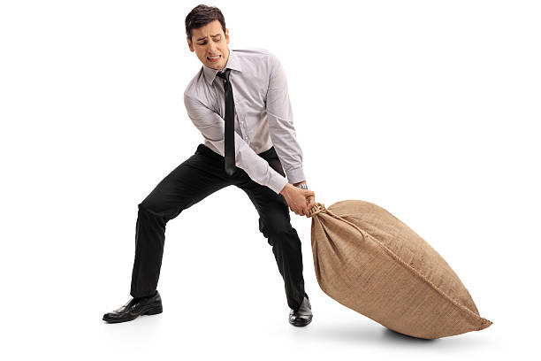 Young businessman pulling a burlap sack stock photo