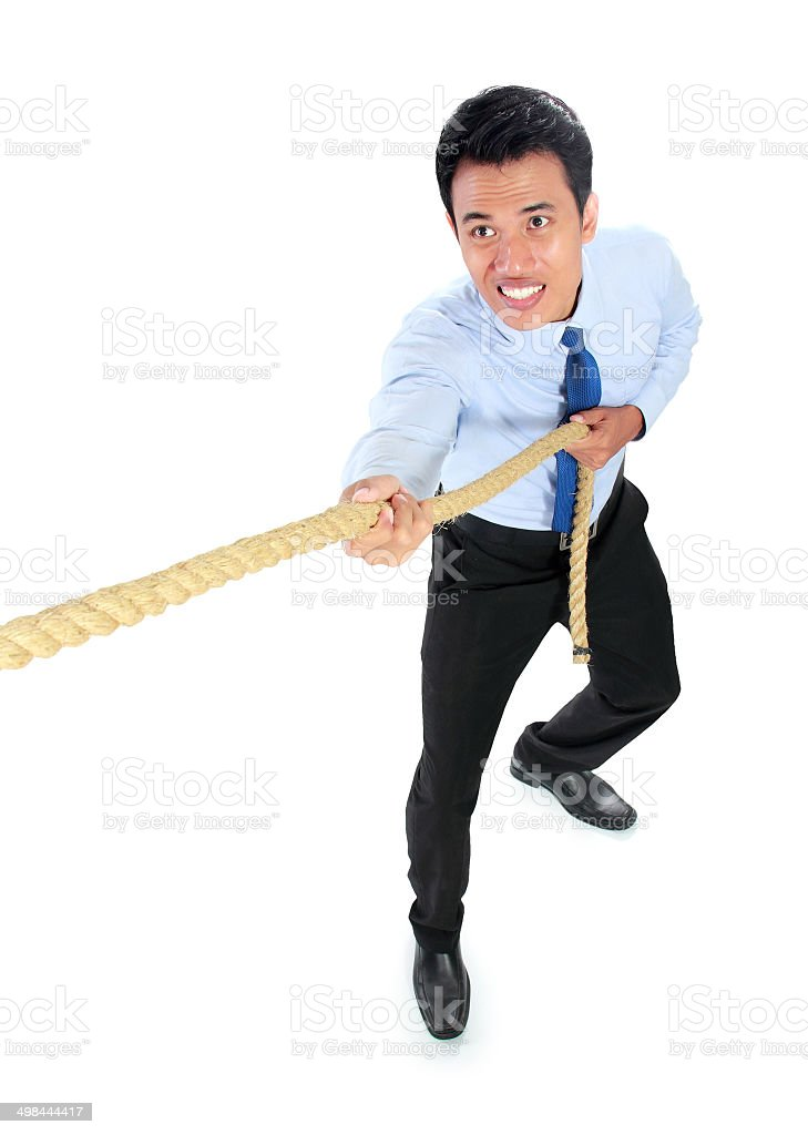 Young businessman pulling a rope while standing stock photo