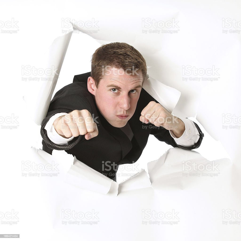 Young businessman punching through paper wall stock photo