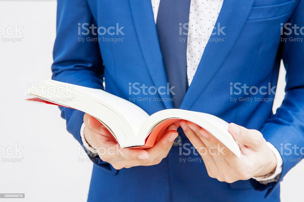 Young businessman reading book in white isolated background stock photo