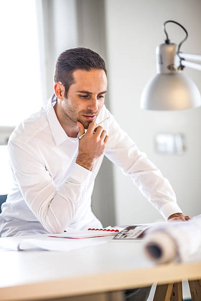 Young businessman reading brochure at desk in office – Foto
