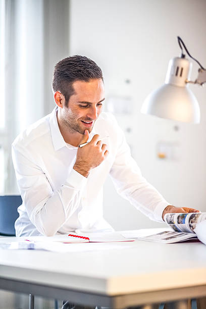 Young businessman reading brochure in office – Foto
