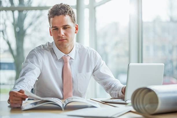 Junger Geschäftsmann liest Broschüre und benutzt Laptop am Schreibtisch – Foto
