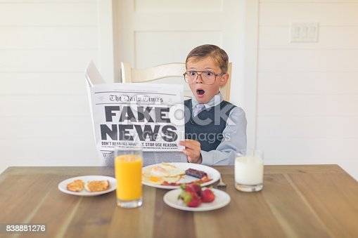 A young buisnessman dressed in a business suit is sitting at the dining room table with a great American breakfast of eggs, bacon, toast and orange juice while he is reading the shocking version of fake news. Can the media be trusted anymore?