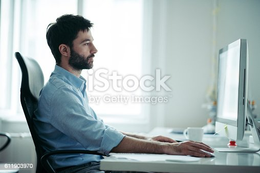 istock Young businessman reading mail 611903970