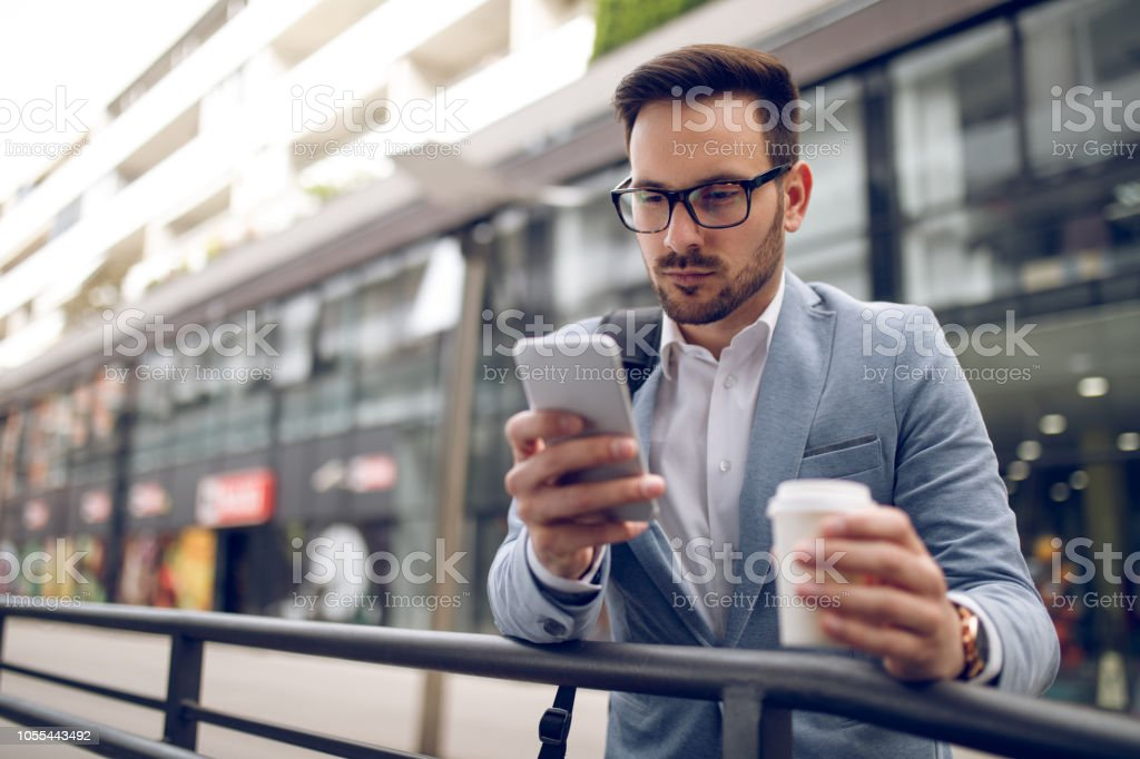 Young businessman reading text message on mobile phone