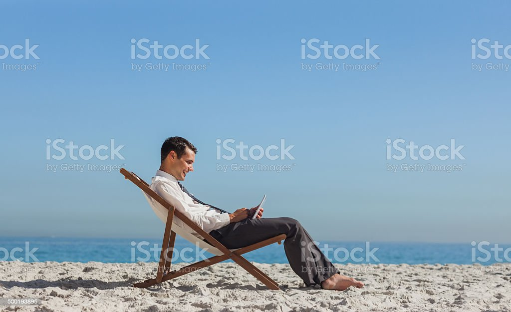 49ec9e8e03 Young Businessman Resting On His Deck Chair Using His Tablet Stock ...