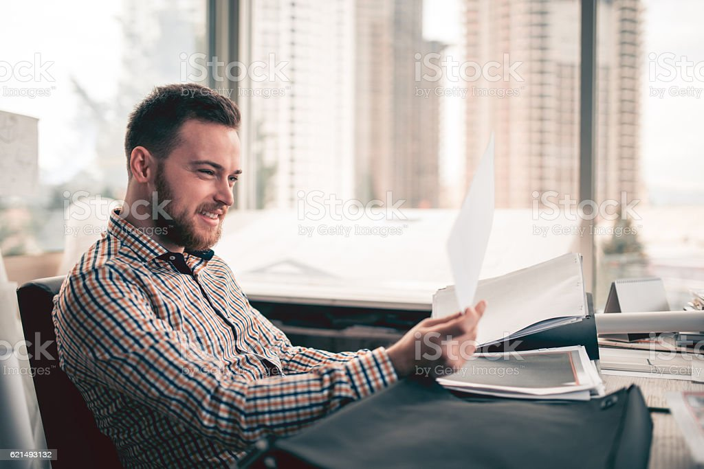 Young Businessman Reviewing Plans at Blue Prints on Desk photo libre de droits