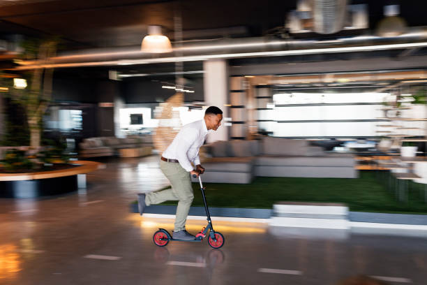 Young businessman riding scooter inside office reception stock photo
