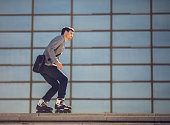 Young businessman going to work on roller skates.