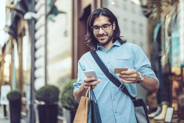 young businessman shopping in the city - indian man stock photos and pictures