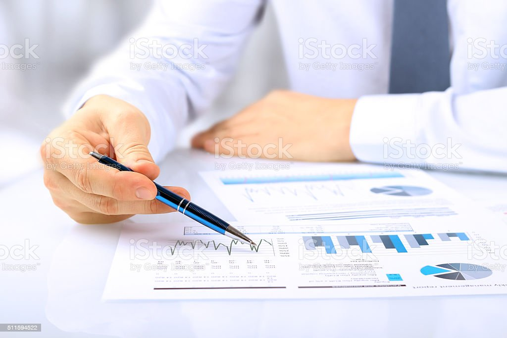 young businessman showing graphs by pen bildbanksfoto