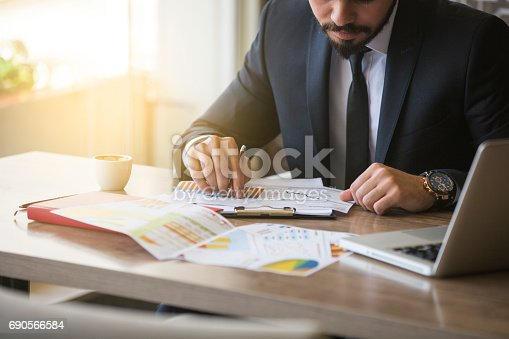 istock Young businessman showing graphs by pen 690566584
