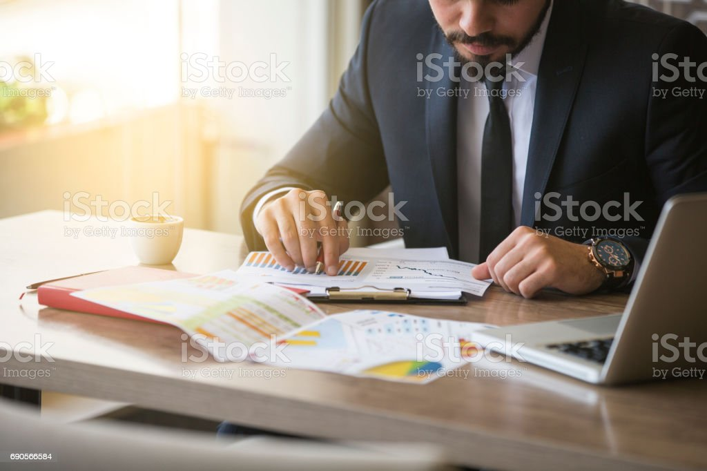 Young businessman showing graphs by pen stock photo