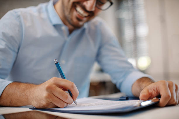 Young businessman signing a contract Young businessman signing a contract signing stock pictures, royalty-free photos & images
