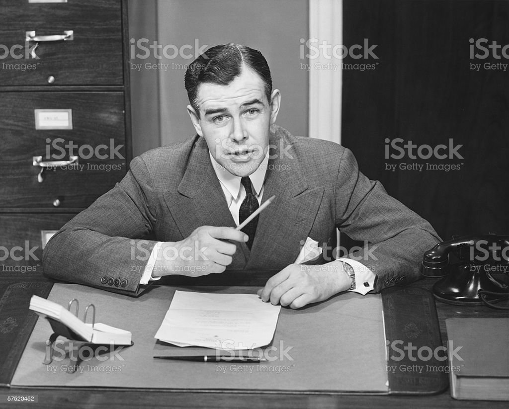 Young businessman sitting at small desk, holding pencil, (B&W) royalty-free stock photo