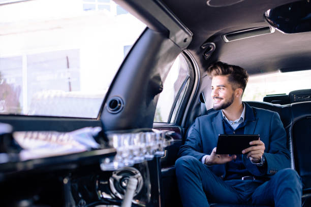 Young businessman sitting in limo Young businessman sitting in limousine millionnaire stock pictures, royalty-free photos & images