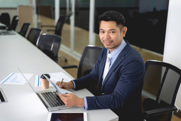 Young businessman sitting in meeting room and smiling stock photo
