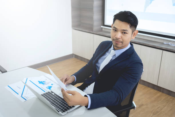 Young businessman sitting in meeting room stock photo