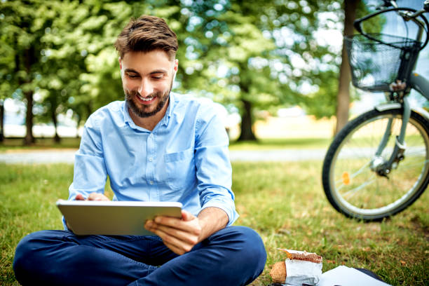 Young businessman sitting on grass in park with tablet and bicycle stock photo