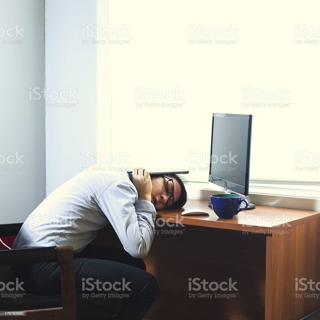 Young Businessman Sleeping At Computer Desk royalty-free stock photo