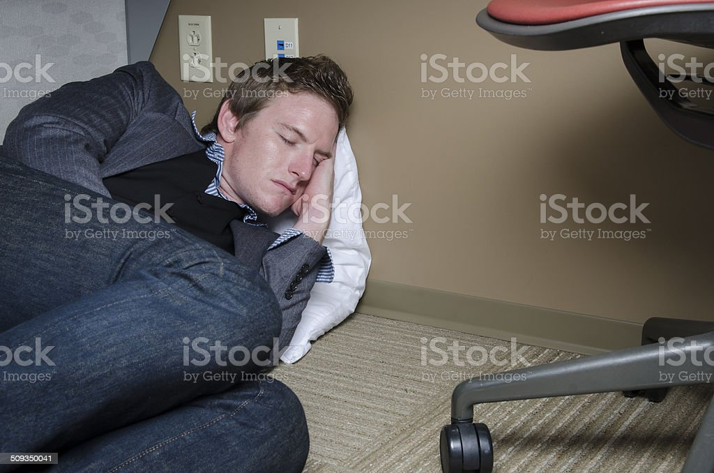Young Businessman Sleeping Under His Desk stock photo