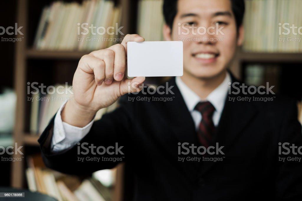 Junger Geschäftsmann Lächeln und hält leere Visitenkarte im Büro, Business-Konzept – Foto