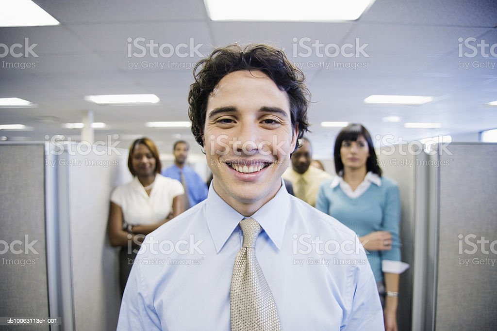 Young businessman, smiling, colleagues in background foto de stock royalty-free