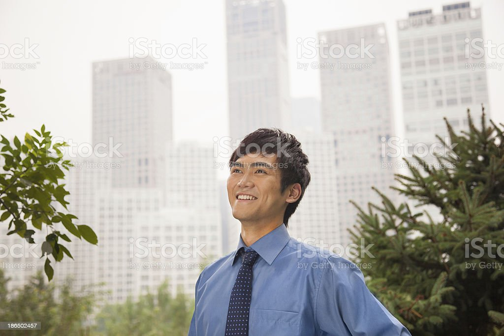 Young businessman smiling in the park, portrait royalty-free stock photo