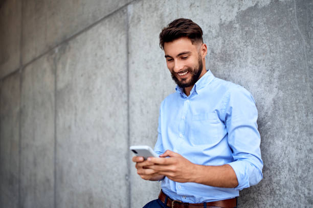 Young businessman smiling while texting on smartphone in the city stock photo