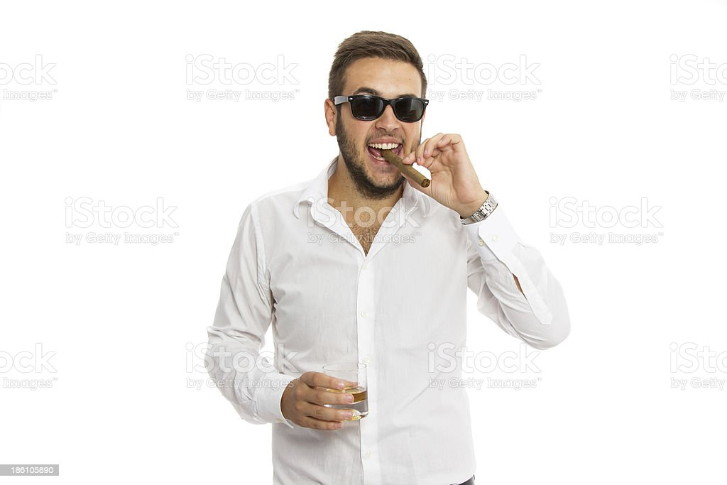 Young businessman smoking cigar and drinking whiskey royalty-free stock photo