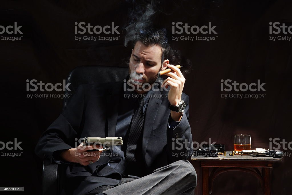 Young businessman smoking on dark background stock photo