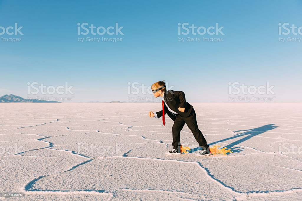 Young Businessman Speeds with Fire through Desert stock photo