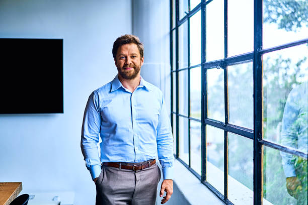 Young businessman standing by some windows in a modern office stock photo