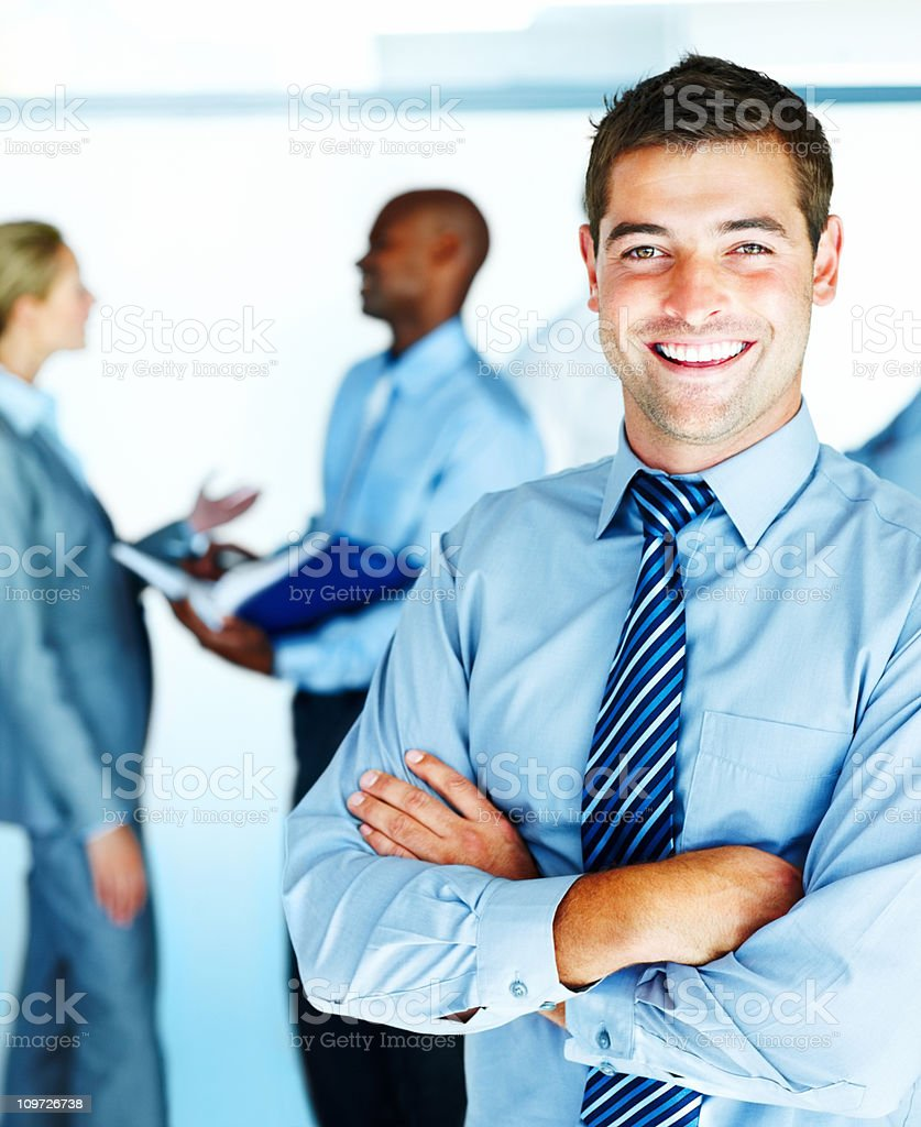Young businessman standing hands crossed with business people in background royalty-free stock photo
