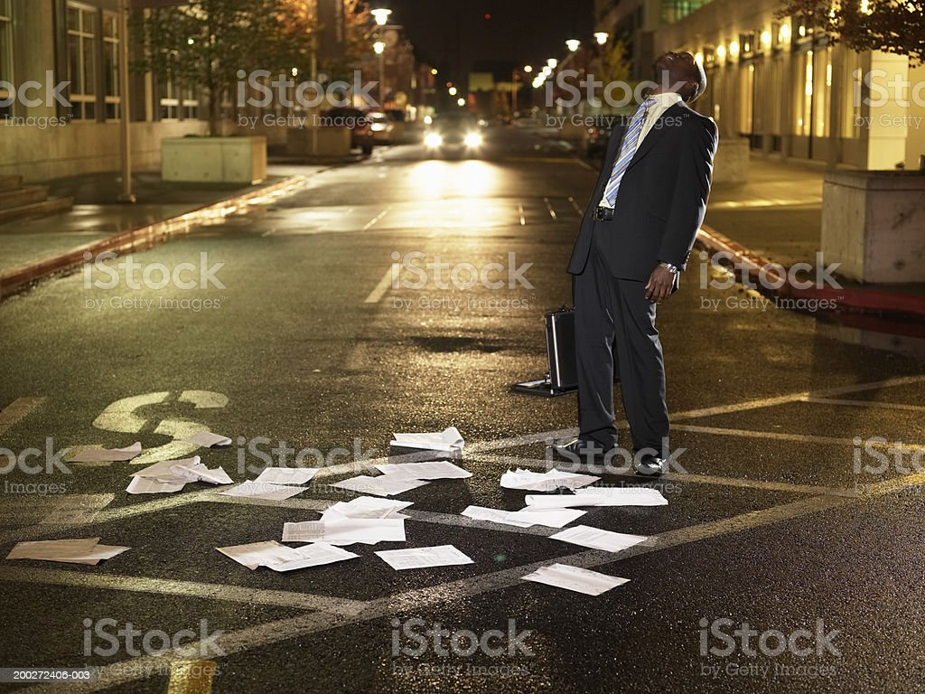 Young businessman standing in crosswalk, papers scattered on ground royalty-free stock photo