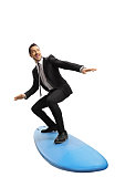 Full length shot of a young businessman standing on a surfing board isolated on white background