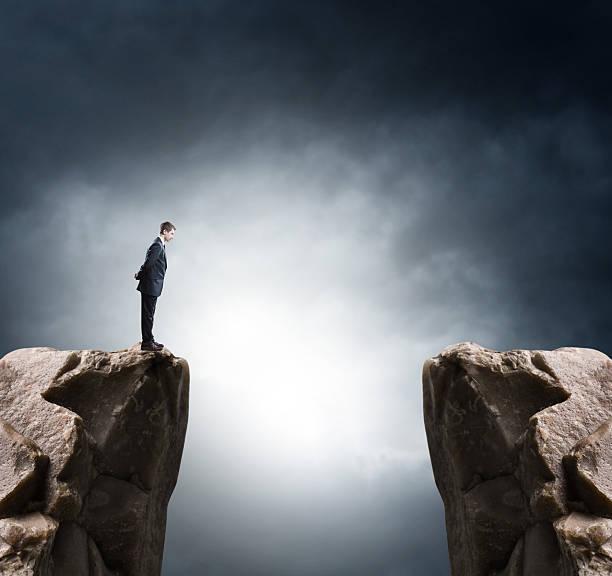 młody biznesmen stojące na krawędzi skał i patrzy na góry - klif zdjęcia i obrazy z banku zdjęć