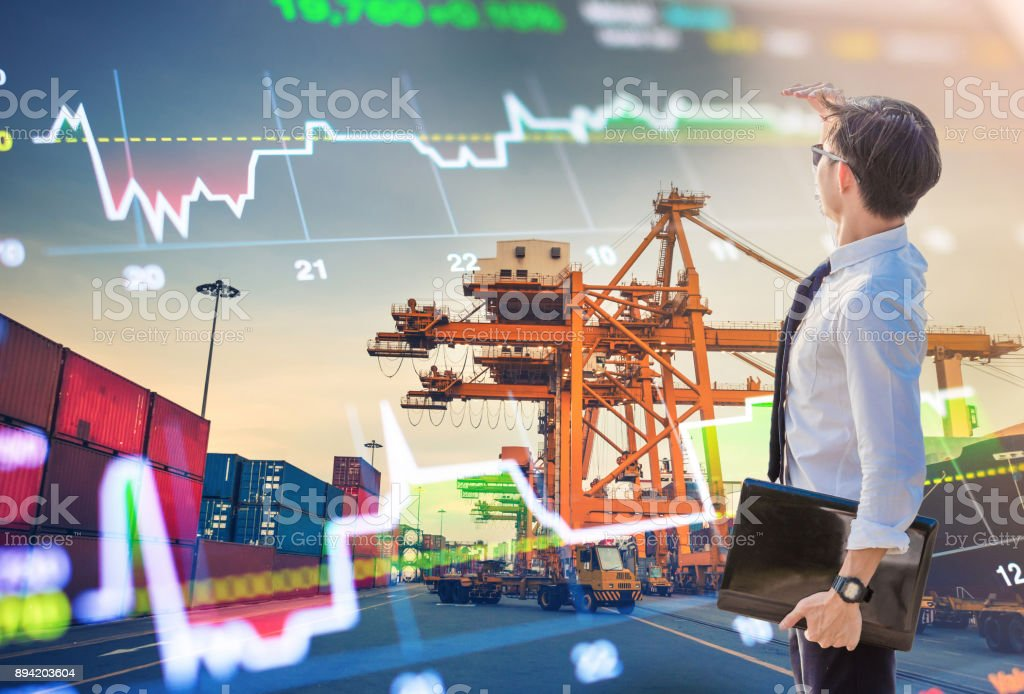 Young businessman standing on port with crane and cargo working stock photo
