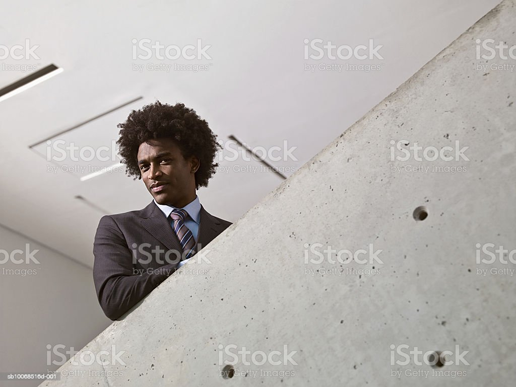 Young businessman standing on stairs, portrait 免版稅 stock photo