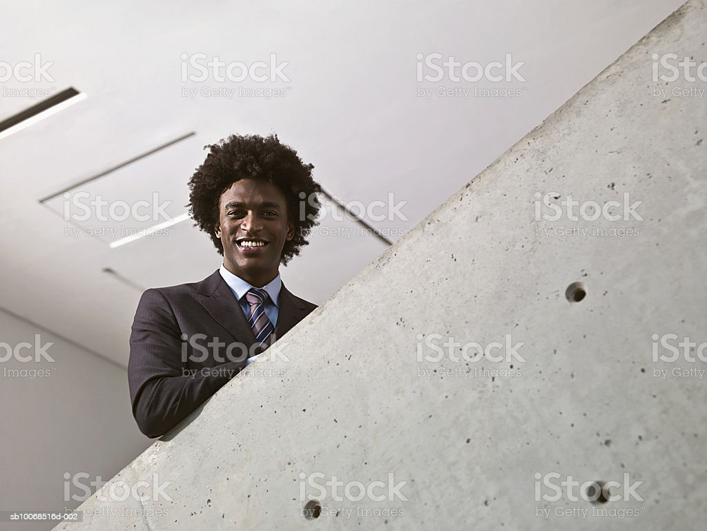 Young businessman standing on stairs, smiling, portrait foto royalty-free