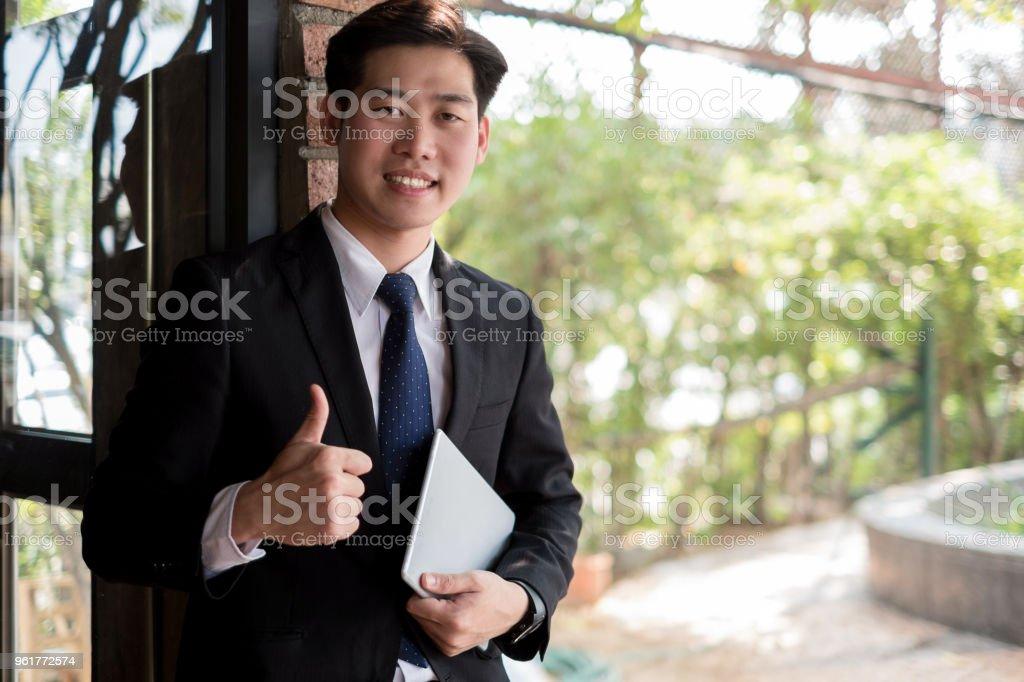 Junger Geschäftsmann stehenden Daumen mit Tablet-PC in der Nähe von Büro, Business-Konzept – Foto