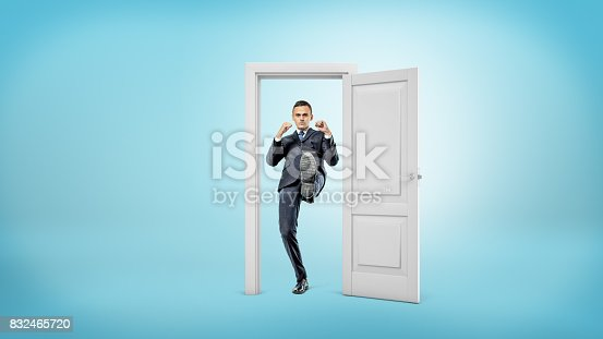 istock A young businessman stands in a small cut out doorframe and kicks a door open with his foot 832465720