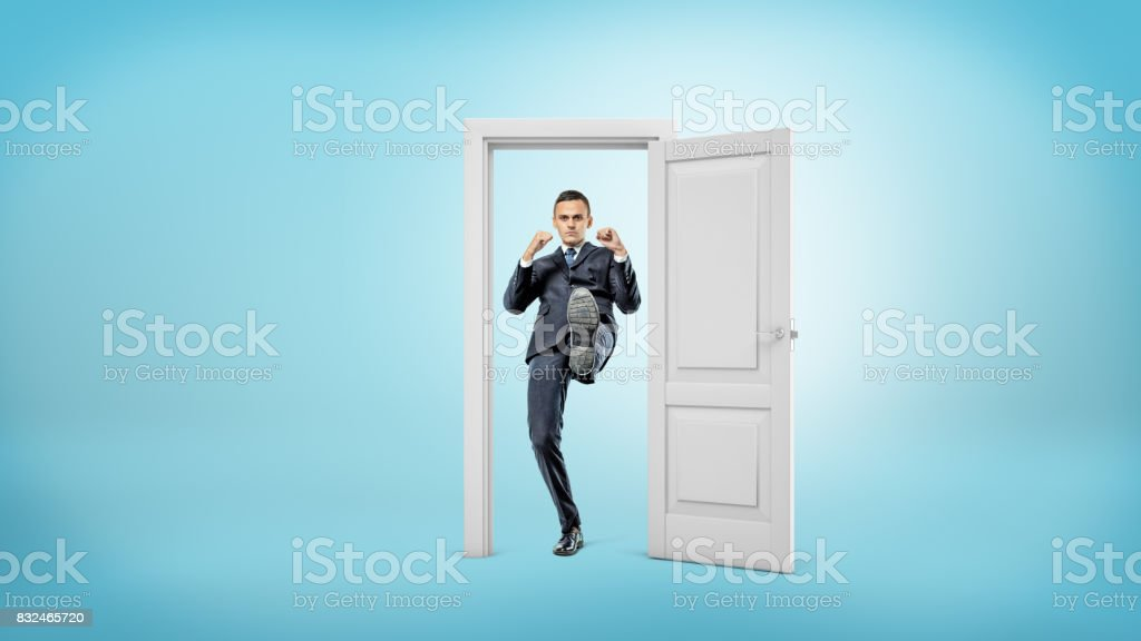 A young businessman stands in a small cut out doorframe and kicks a door open with his foot stock photo