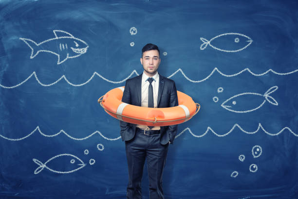 A young businessman stands inside an orange life buoy on a blue background with chalk waves and fish. stock photo