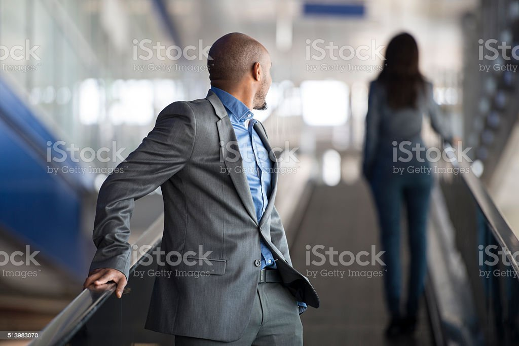 Young businessman staring at woman on escalator. stock photo