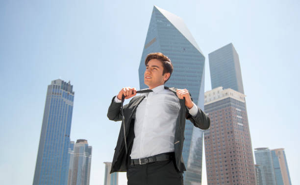 young businessman takes off his tie in front of skyscraper stock photo