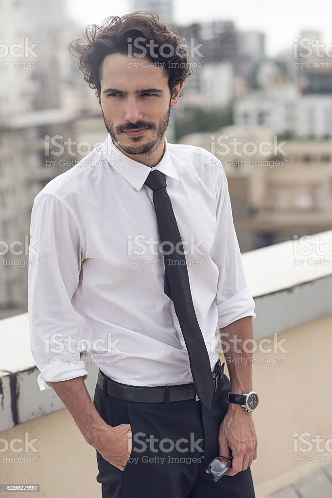 young businessman taking a break from work on the balcony stock photo