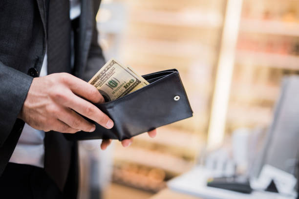 young businessman taking money out of his wallet - spending money stock pictures, royalty-free photos & images